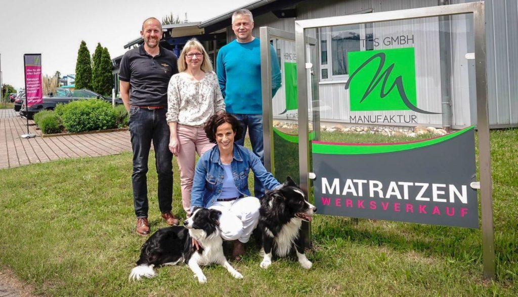 Das komplette Team der Firma Matratzen Ultes GmbH in Landstuhl vor dem Ausstellungsraum mit Logo